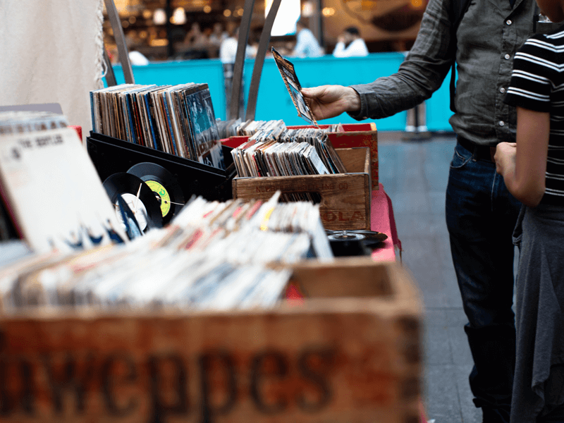 Men browsing vinyl records on stall