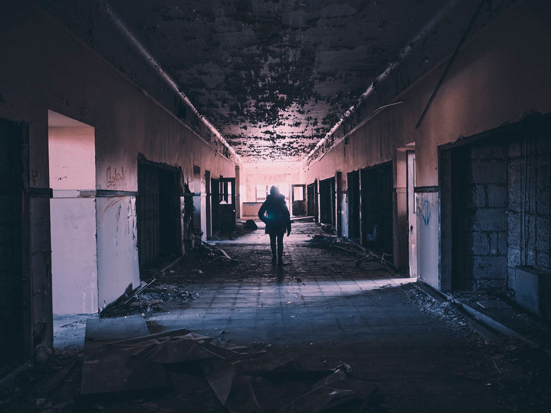 Person in abandoned, derelict hallway
